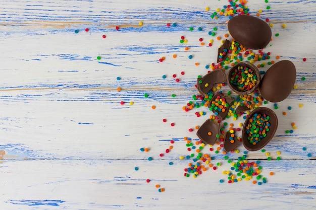 Uova di cioccolato pasquali, dolci multicolori sulla superficie in legno bianco. concetto di pasqua. vista piana, vista dall'alto