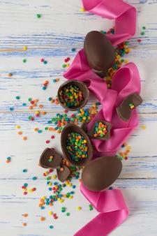 Uova di cioccolato pasquali, nastro rosa, dolci multicolori sulla vecchia superficie di legno bianca. concetto di pasqua