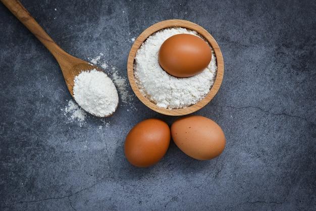 Uova di farina fatte in casa cottura ingredienti sul tavolo da cucina farina di pasticceria sulla ciotola di legno su grigio, vista dall'alto
