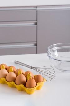 Uova di fronte nel cartone giallo; frusta e ciotola di vetro sul tavolo bianco