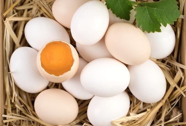 Uova di gallina bianche e marroni con un uovo rotto al centro.