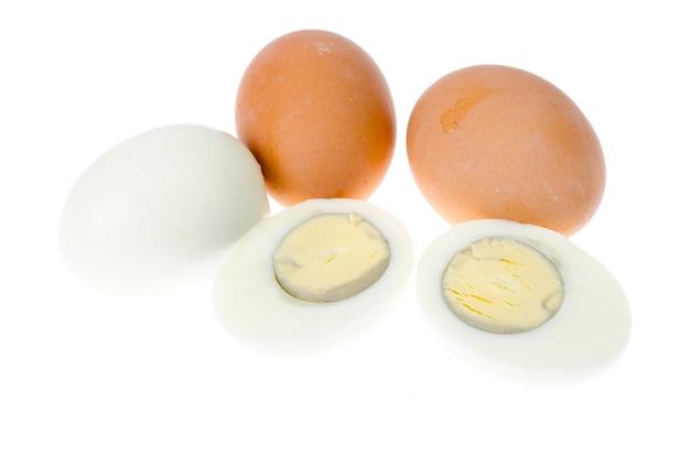 Uova di gallina bollite con conchiglie colorate su superficie bianca