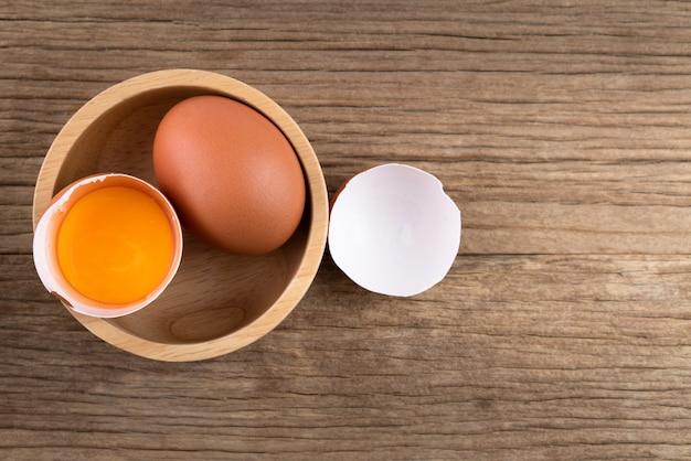 Uova di gallina crude su fondo di legno rustico