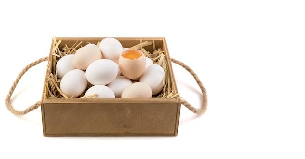 Uova di gallina di colore bianco e marrone con un uovo rotto al centro.