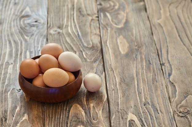 Uova di gallina fresche del villaggio su fondo di legno scuro. entourage di pasqua. cesto o presa. testo libero, copia spazio.