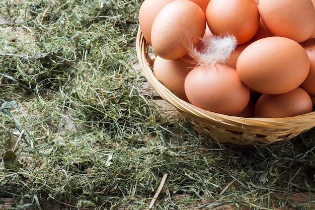 Uova di gallina fresche in un cestino su paglia nell'azienda agricola. stile rustico.