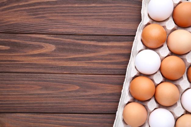 Uova di gallina in contenitori su fondo di legno marrone
