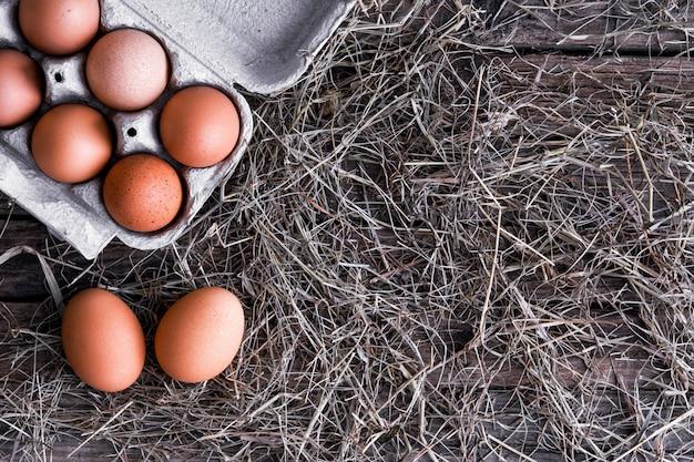 Uova di gallina in un nido di vimini e in una scatola in un pollaio vista dall'alto.