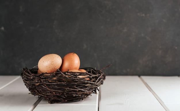 Uova di gallina in un nido di vimini su uno sfondo grigio scuro. spazio della copia di pasqua