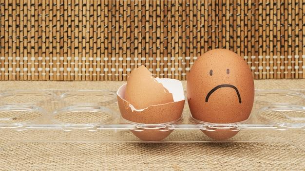Uova di gallina in un portauovo. mezzo uovo, tuorlo d'uovo, guscio. emozione ed espressione facciale dipinte sulle uova.