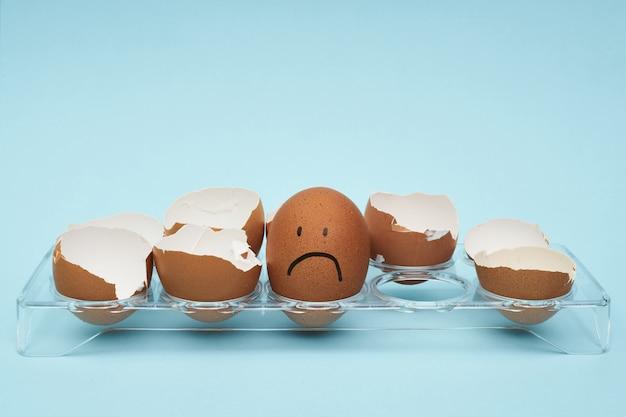 Uova di gallina in un portauovo. vassoio pieno di uova. emozione ed espressione facciale dipinte sulle uova