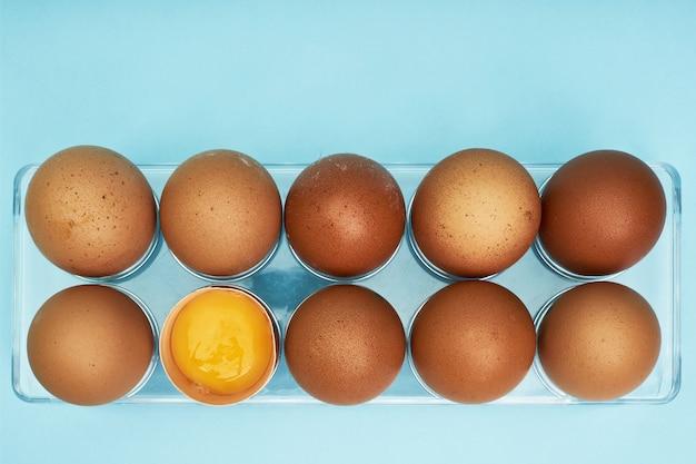Uova di gallina in un portauovo. vassoio pieno di uova. mezzo uovo, tuorlo d'uovo, guscio.
