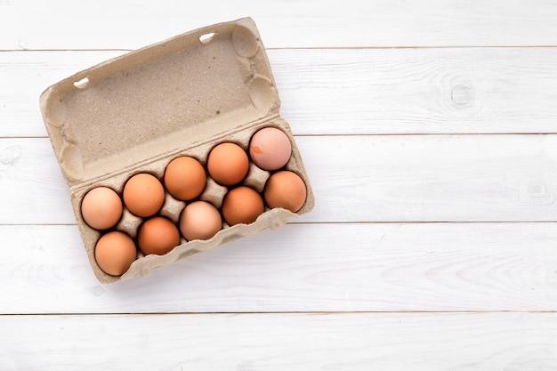 Uova di gallina in un vassoio su uno sfondo bianco dalle schede. uova di gallina in un vassoio