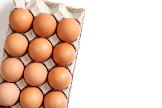 Uova di gallina in una scatola di cartone su bianco. alimenti biologici vista dall'alto