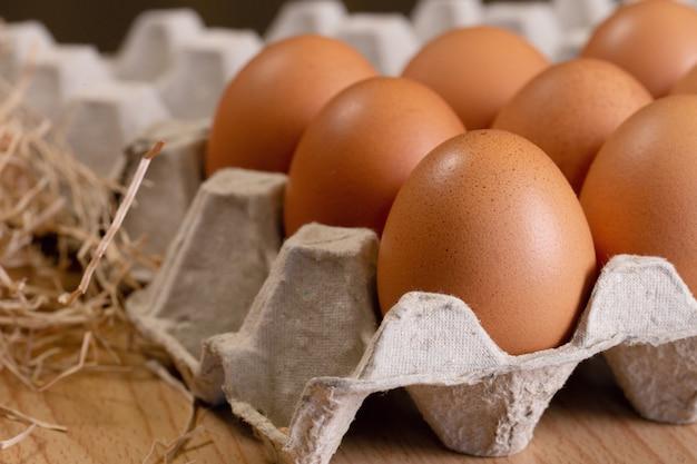 Uova di gallina in una scatola di cartone su un marrone di legno. cibo organico