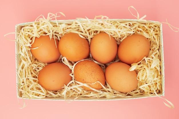 Uova di gallina in una scatola su uno sfondo rosa pastello, copie di spazio, flatlay