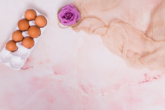 Uova di gallina marrone in rack con fiore