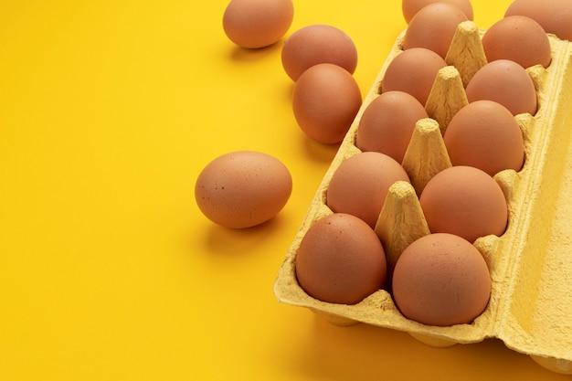 Uova di gallina marrone in scatola di cartone, insegna delle uova fresche dell'azienda agricola sulla vista gialla e superiore con lo spazio della copia per testo