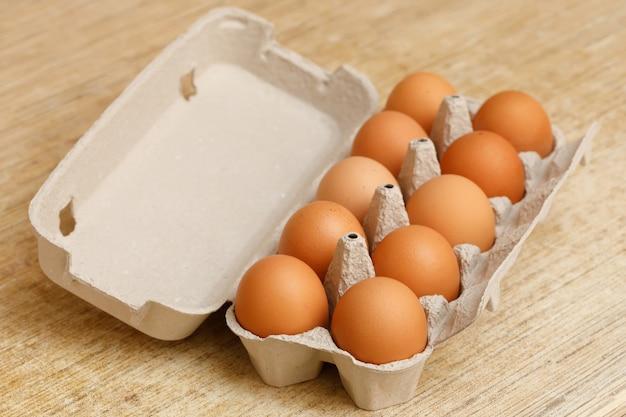 Uova di gallina marrone in scatola di cartone sul tavolo di legno