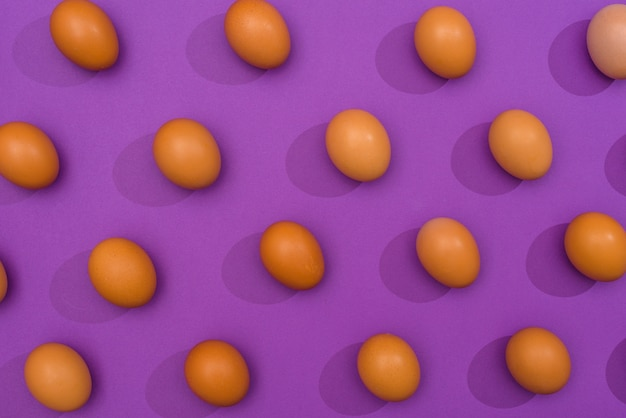 Uova di gallina marrone sparse sul tavolo viola
