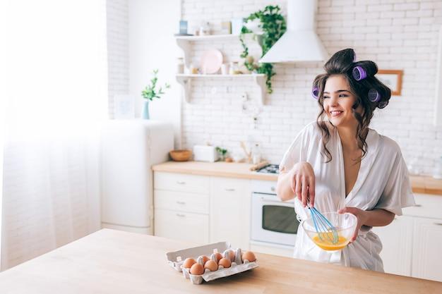Uova di mescolanza della bella giovane casalinga piacevole allegra in cucina. guardando a lato e sorridendo. uova in contenitore sulla tavola. moglie negligente senza lavoro. daylight.