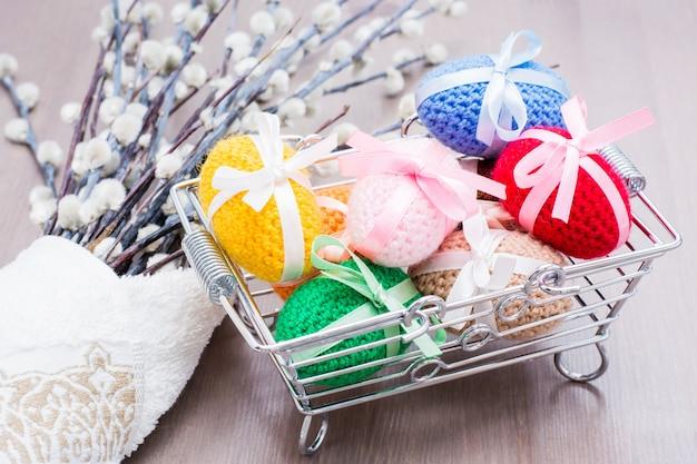 Uova di pasqua a maglia legate con nastri colorati in un cestino di metallo e salice su un tavolo di legno