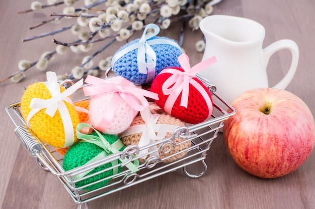 Uova di pasqua a maglia legate con nastri colorati in un cestino di metallo, una mela, una brocca e salice su un tavolo di legno
