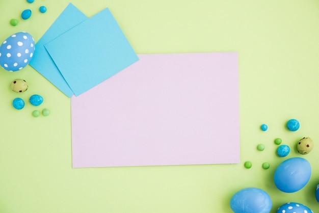 Uova di pasqua blu con fogli di carta bianca sul tavolo verde
