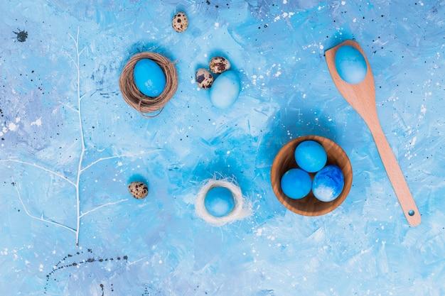 Uova di pasqua blu in nidi sul tavolo