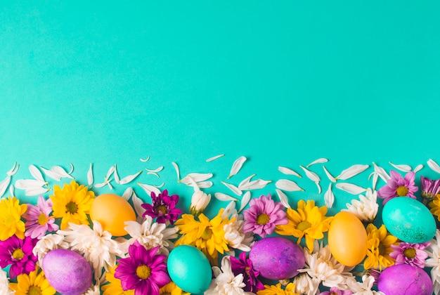 Uova di pasqua brillanti e boccioli di fiori freschi