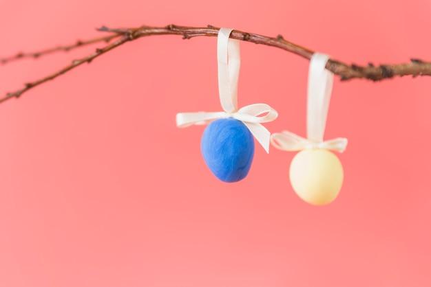 Uova di pasqua che appendono sul ramoscello