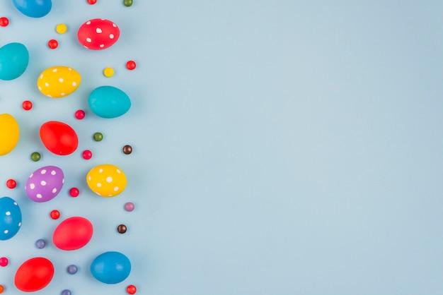 Uova di pasqua colorate con caramelle sul tavolo