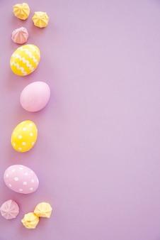 Uova di pasqua colorate con dolci sul tavolo viola