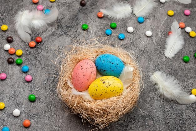 Uova di pasqua colorate con piume e dolci nel nido