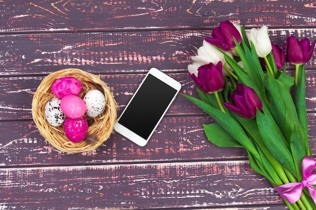 Uova di pasqua colorate, fiori di tulipano e smartphone
