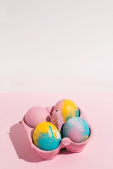 Uova di pasqua colorate in piccola cremagliera su rosa in grado