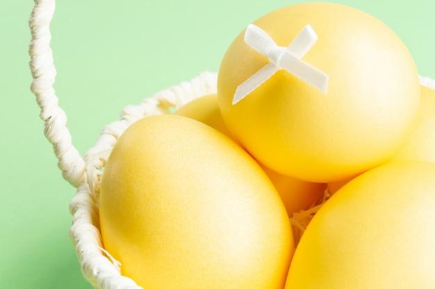 Uova di pasqua colorate in un cestino bianco. sfondo verde concetto di vacanza di pasqua.
