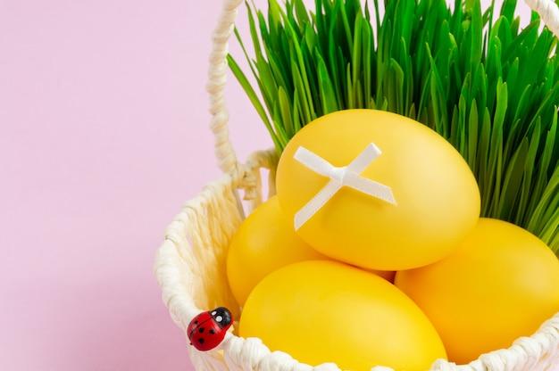 Uova di pasqua colorate in un cesto bianco con verdi decorativi