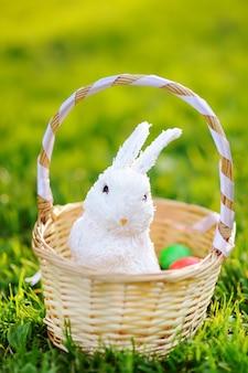 Uova di pasqua colorate in un cesto con coniglietto carino giocattolo bianco