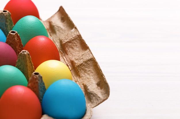 Uova di pasqua colorate multi in una scatola su una tavola.