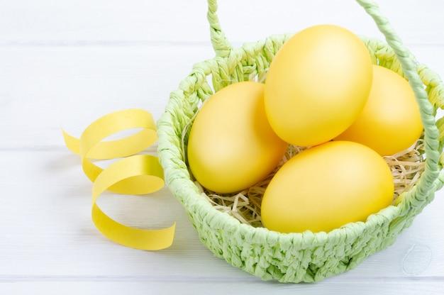 Uova di pasqua colorate nel cestino verde. fondo in legno bianco concetto di vacanza di pasqua.