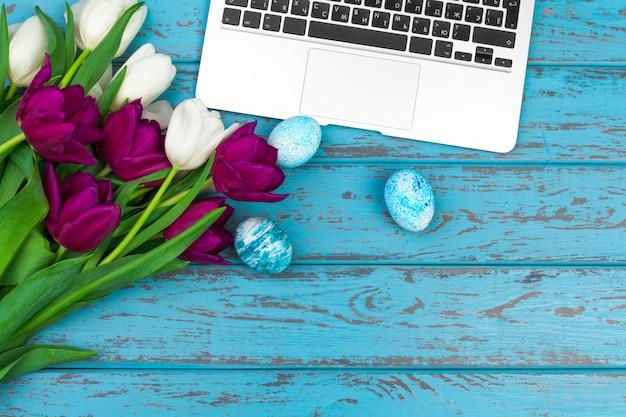 Uova di pasqua, computer portatile e mazzo di tulipani.