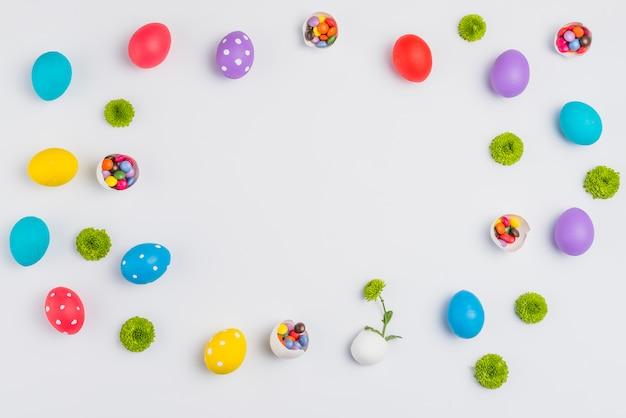 Uova di pasqua con caramelle e fiori sparsi sul tavolo bianco