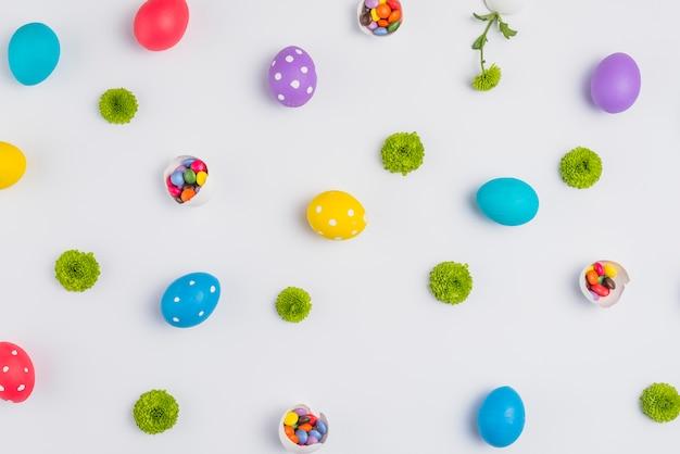 Uova di pasqua con caramelle e fiori sparsi sul tavolo