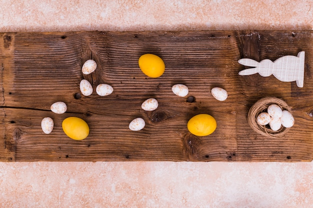 Uova di pasqua con coniglio bianco sul tavolo