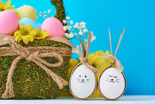 Uova di pasqua con facce dipinte e cestino decorativo su un bacground blu