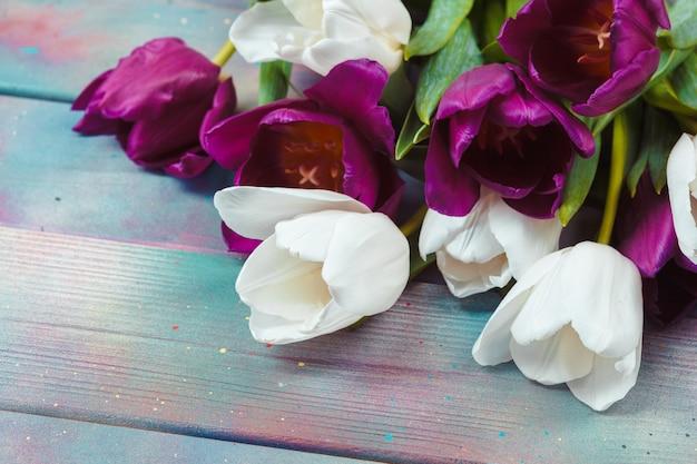 Uova di pasqua con i tulipani su di legno blu