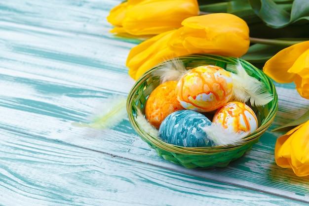Uova di pasqua con i tulipani sulla tavola di legno blu