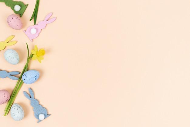 Uova di pasqua con la figura del coniglio e il fiore del narciso.