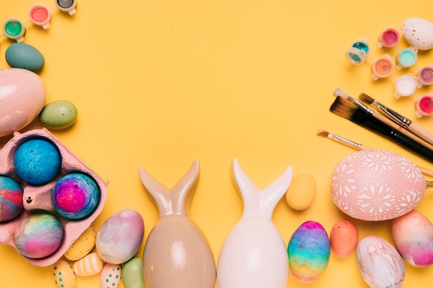 Uova di pasqua con orecchie da coniglio e pennelli con spazio per scrivere il testo